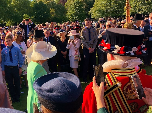 Charles and Camilla on a walk past, being sturdily guarded by a Beefeater